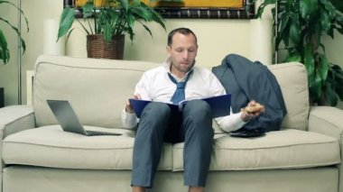 Businessman reading documents and eat sandwich on sofa at home — Vídeo stock