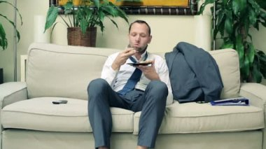 Businessman eating sandwich on sofa at home — Stock Video