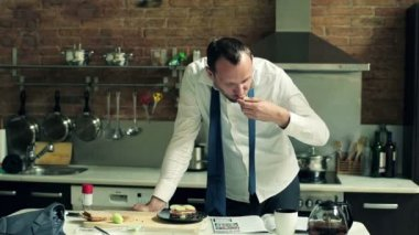 Businessman eating sandwich and reading newspaper in the kitchen — Stock Video