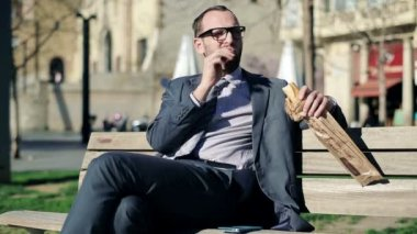Young handsome businessman eating baguette in the city — Stock Video