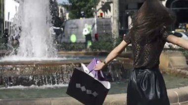 Happy woman with shopping bags by the fountain in the city — Stok video