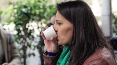 Pensive woman drinking coffee in outdoor cafe — Stock Video