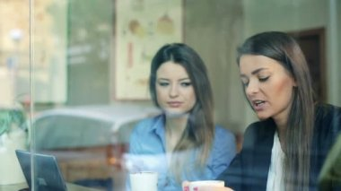 Young businesswomen and businessman talking during coffee break in cafe — Stock Video