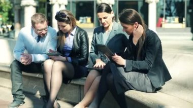 Group of young business people with tablet, laptop and smartphone in the city — Stock Video