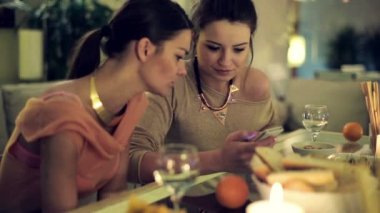 Two girlfriends with smartphone by the dinner table at party — Stock Video