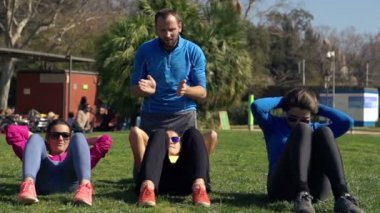 Young women doing sit ups with personal trainer — Stock Video