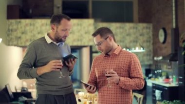 Two friends with smartphones talk and drink wine on party — Stock Video