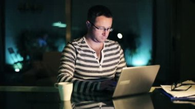 Man surfing web on laptop in dark room at night — Vidéo