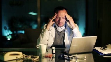 Overworked doctor having headache, working late at night — 图库视频影像