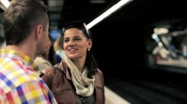Happy young couple talking while waiting on subway station — Stock Video