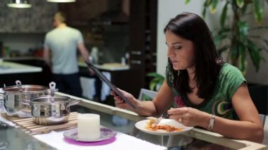 Woman eating dinner, surfing web on tablet computer by the table at home — Stock Video