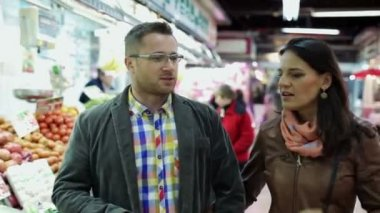 Couple shopping, looking at vegetables in vegetable market — Stock Video