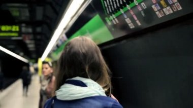 Two young girlfriends talking and looking at metro map — Stock Video
