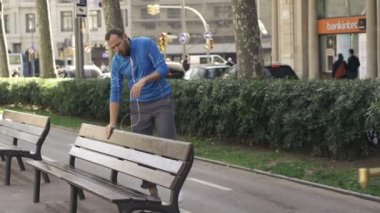 Jogger resting by bench in the city — Stock Video
