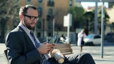 Businessman listening music on smartphone and eating baguette in the city — Stock Video