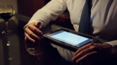 Businessman checking financial data on tablet computer late at night — Stock Video