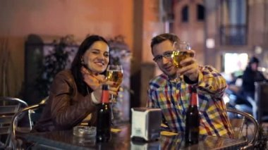 Young couple raising toast to camera in outdoor bar at night — Vídeo Stock