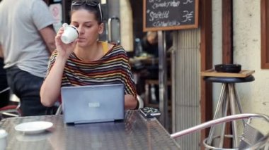 Woman with laptop computer drinking coffee in cafe — Stockvideo
