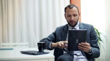 Businessman drinking coffee and using tablet computer on terrace — Stock Video