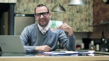 Happy young businessman holding, shaking euro bills, money by the desk — Stock Video