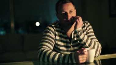 Pensive, thoughtful man sitting by the table in dark room at night — Vídeo stock