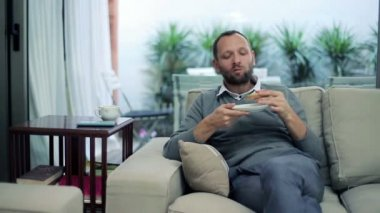 Man eating sandwich and drinking tea while sitting on sofa at home — Stock Video
