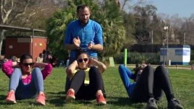 Young women doing sit ups with personal trainer in the park — Stock Video