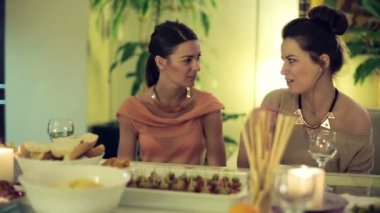Two girlfriends chatting by dinner table at home — Stock Video