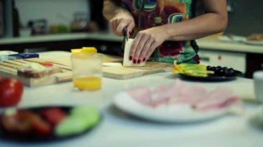 Woman slicing yellow cheese, preparing breakfast in kitchen — Stock Video