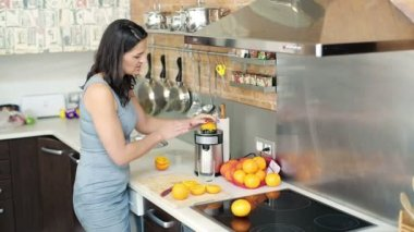 Businesswoman in kitchen preparing and drinking fresh orange juice — Stock Video
