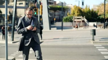 Young businessman with smartphone crossing city street — Stock Video