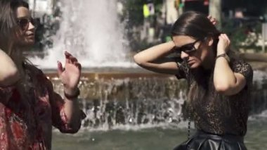Girlfriends talking, gossip by the fountain in the city — Stock Video