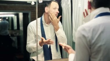 Businessman applying moisturizing cream on his face in bathroom — Stock Video