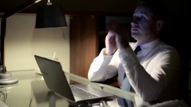 Tired businessman taking nap by the desk late at night — Stockvideo