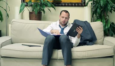 Businessman working with tablet computer and documents on sofa — Stock Video