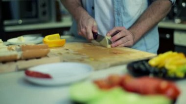 Man slicing cheese on table in kitchen — Stock Video