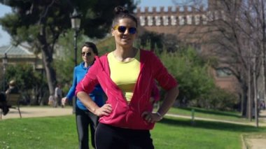 Young happy female jogger in the park — Stock Video