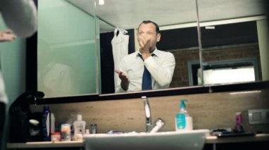 Businessman applying moisturizing cream on his face in bathroom — 图库视频影像
