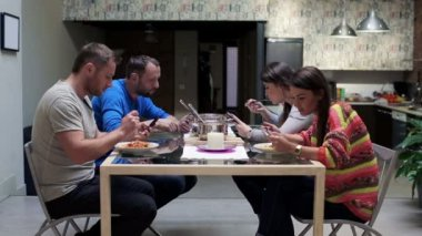 Young group of friends with smartphones during dinner at home — Stock Video