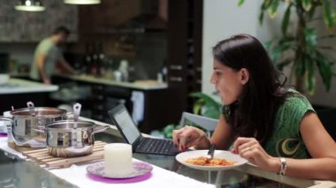 Woman eating tasty dinner and surfing internet on laptop at home — Stock Video