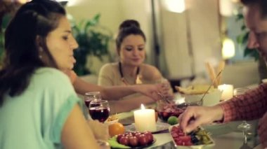 Young four friends chatting during evening dinner at home — Stock Video