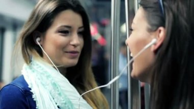 Happy girlfriends listen to music and singing while ride metro train — Stock Video