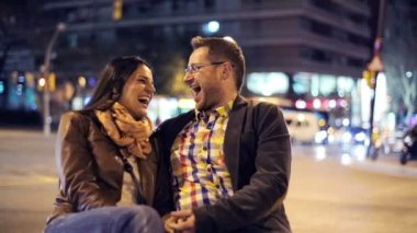 Happy, laughing young couple by the city street at night — Stock Video