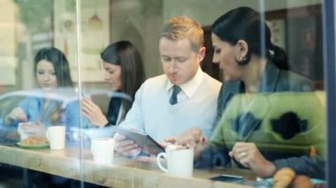 Business people with tablet and smartphone chatting in cafe — Stock Video