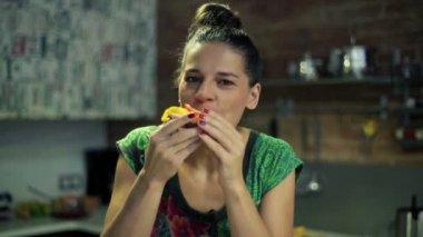 Happy woman eating tasty sandwich in kitchen — Stock Video