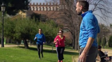 Joggers in the park, running, stretching — Stock Video