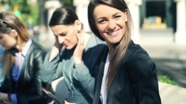 Portrait of young beautiful businesswomen sitting in the city — Stock Video