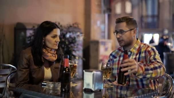 Enojado pareja discutiendo en el bar al aire libre en la ciudad — Vídeo de stock