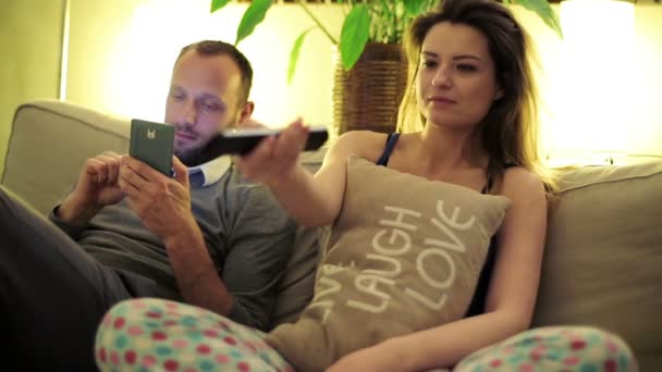 Young couple on sofa watching funny comedy tv at home — Vidéo