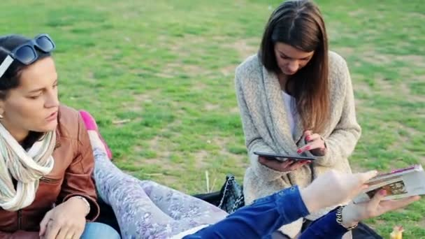 Girlfriends with tablet relaxing, reading guide book on the grass in the park — Vidéo